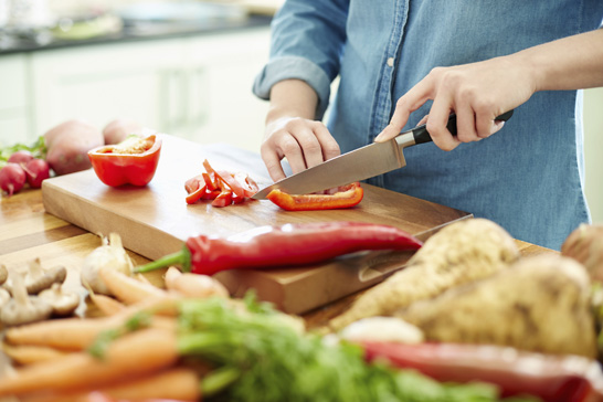 Midsection image of woman chopping red bell pepper on cutting board. There are various vegetables on wooden table. Focus is on her hands. Female is preparing food. She is in domestic kitchen.