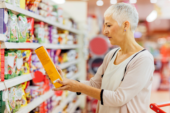 Mature woman shopping in local supermarket. Standing by produce stand and choosing cereals. Holding box and reading nutrition label.